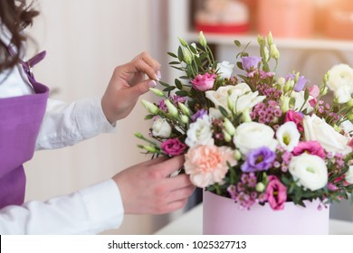 Florist workplace. Young woman arranging a beautiful bouquet with white roses, eustomas, leaves, ranunculus flowers and gypsophila in flower shop.