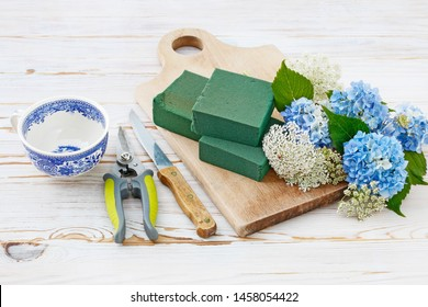 Florist at wotk: How to make floral arrangement with blue hortensia (hydrangea) and white Queen Anne's lace (daucus carota) flowers on white wooden table. Step by step, tutorial.
