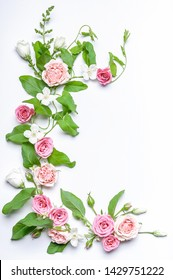 Floristic vertical wedding composition: bindweed leaves, flowers and rosebuds, white jasmine flowers on a white background. Top view