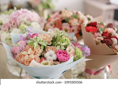 Floristry concept. Four bouquet of beautiful flowers on gray table. Spring colors. the work of the florist at a flower shop.