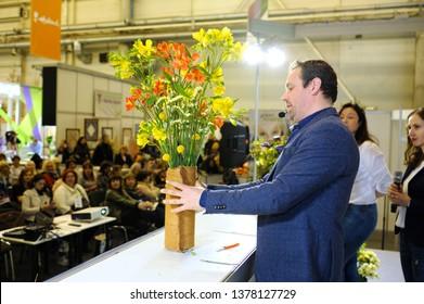 Floristry lesson. Florist arranging bouquet of flowers on a stage, an audience watching. April 17, 2019. Exhibition Flower Expo Ukraine. Kiev, Ukraine