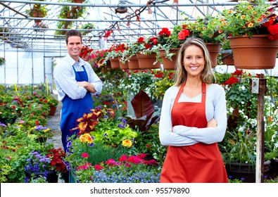 Florists couple working with flowers at a greenhouse.