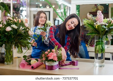 Florists create bouquets for wedding. Soft shades of fresh spring flowers, wrapped in decorative paper or placed in box. Floristry business.