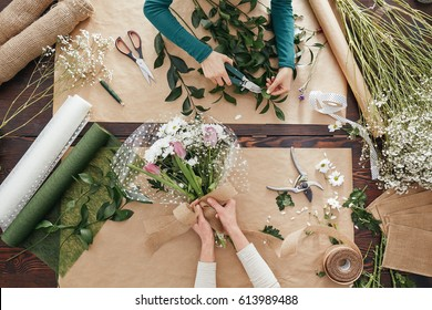 Florists making flower bouquets on a wooden table