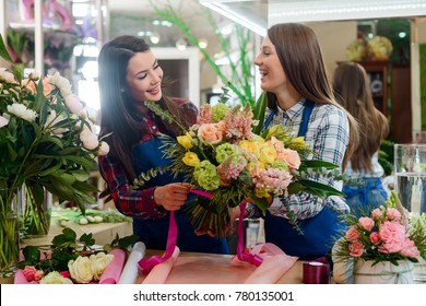 Florists tying a bouquet with satin ribbon. Beautiful flowers for mom on Mother's day. Fulfillment of an order, small floristry business.