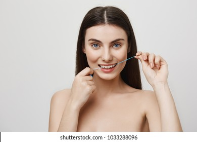 Floss is important for tooth care. Indoor shot of attractive european woman with blue eyes flossing teeth, trying to look after her perfect smile as dentist prescribed, standing over gray wall