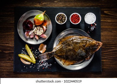 Flounder with herbs served on black stone on wooden table