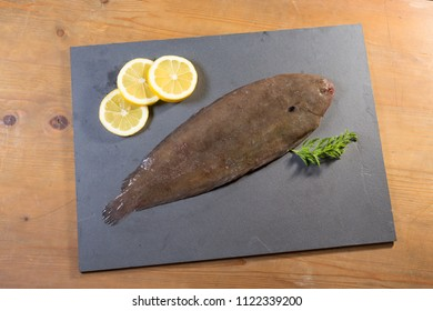 flounder presented on a slate resting on a wooden table