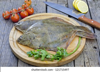 Flounder raw fish on cutting board in kitchen
