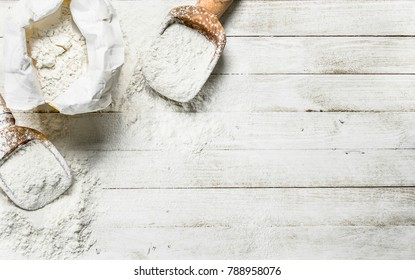Flour in bag with a shovel. On a white wooden table.