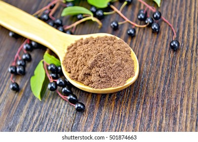 Flour of bird-cherry in a spoon with berries on a background of wooden boards