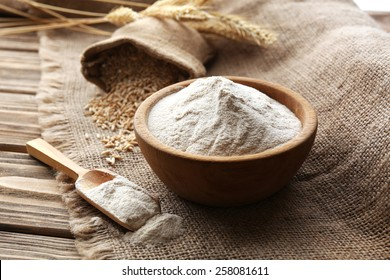 Flour in bowl with ears and grains on sackcloth background