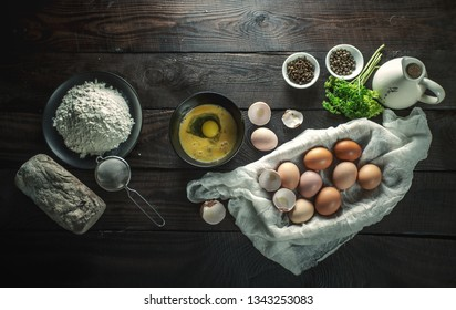 Flour, bread and eggs in a basket on a wooden table, top view.