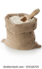 Flour in burlap bag on white background