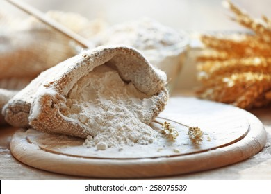Flour in burlap bag on wooden cutting board and blurred background