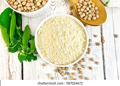 Flour chickpeas and chick-pea in white bowls and spoons, pods of green beans, a doily on the background of wooden boards on top