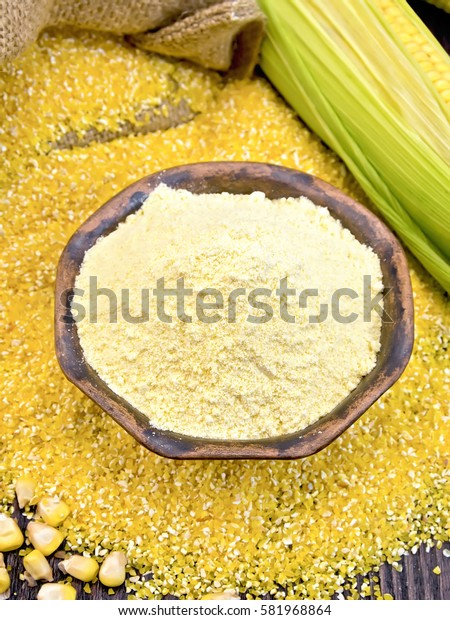 Flour corn in a clay bowl on the grits, cobs and grains, a bag on a wooden boards background