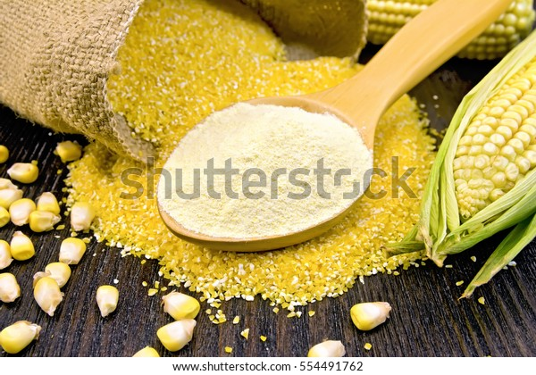 Flour corn in a spoon, cereal in sackcloth and on the table, the cob on the background dark wooden boards