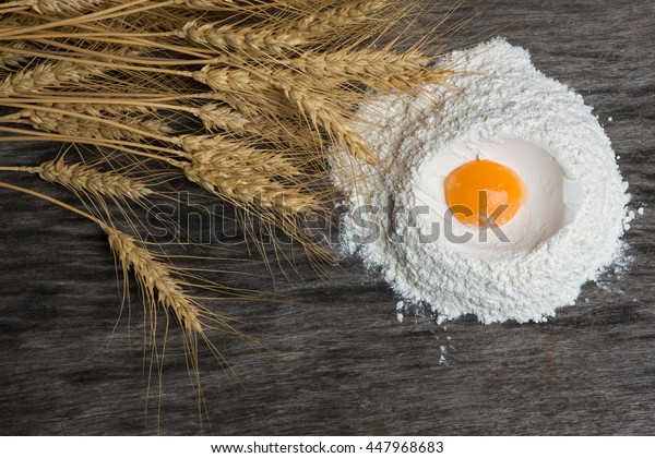 Flour with an egg yolk with ears of wheat on a background of old wood.