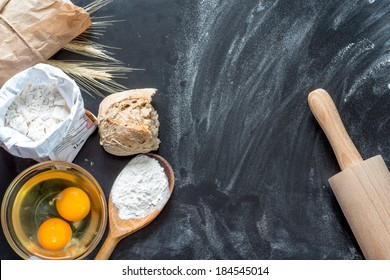 Flour, eggs, and cooking utensils on a wooden cutting board.
