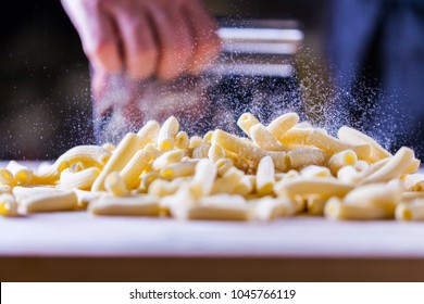 Flour falling over pasta. Falling penne pasta. Rigatoni pasta with flour powder particle falling. Rigatoni Penne Lisce Tortiglioni Doppia Rigatura. Home made rigatoni pasta on the table with flour.