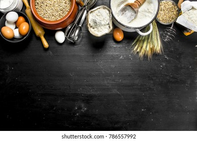 Flour with grains and spikelets of wheat. On the black chalkboard.