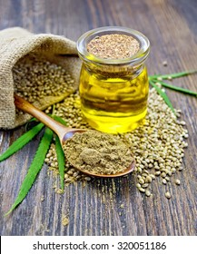 Flour hemp in wooden spoon, seed in a bag and table, oil in glass jar, green leaves cannabis on background of wooden planks