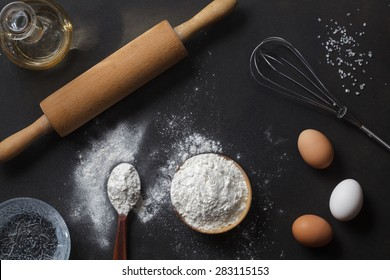 flour and ingredients on black table. Top view