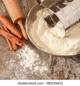 Flour in a metal bowl with  wooden rolling pin on  stone table. Dark rustic style. Square image.