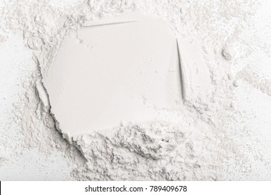 Flour on a colored background. A pile of flour on a white background. Spilled flour