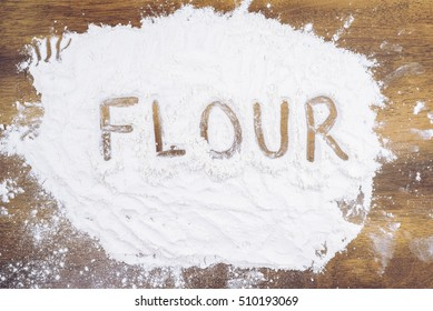 Flour on wooden  table, written out. Cooking concept.