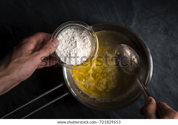 Flour is poured into a saucepan with melted butter close-up