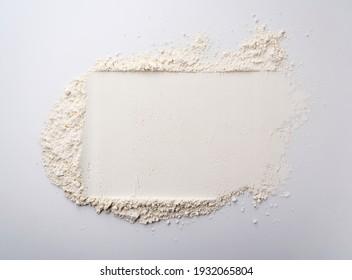 Flour rolled off a rolling pin on a white background. View from directly above.