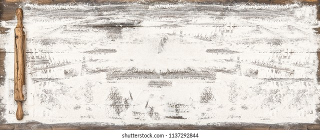 Flour and rolling pin on wooden table. Food background