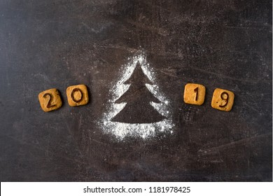 Flour Silhouette Christmas Tree with cookies digits 2019 on dark background with copy space. delicious bakery sweet confectionery Christmas card. Idea of merry new year xmas 2019 holiday
