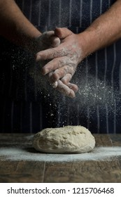 Flour is sprinkled over a ball of dough on a wooden board by hand