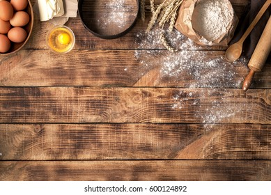 Flour with wheat, eggs, rolling pin, spoon and butter on wooden background, top view with copy space. Ingredients for bakery products