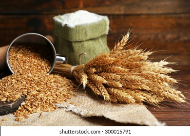 Flour and wheat on wooden background