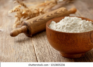flour in a wooden bowl, wooden rolling pin, ears of wheat on an old wooden background