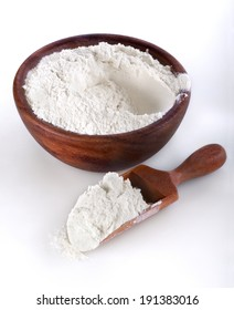 flour in a wooden bowl and shovel on a white background