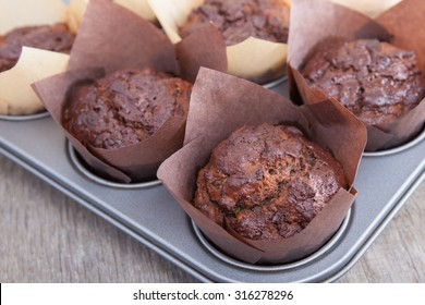 Flourless chocolate courgette muffins made with nut butter in a tin, on wooden table, selective focus
