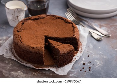 Flourless chocolate and espresso cake on concrete background