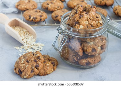 Flourless gluten free peanut butter, oatmeal and chocolate chips cookies in glass jar and on table, horizontal