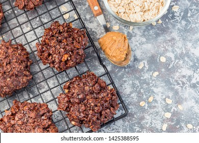 Flourless no bake peanut butter and oatmeal chocolate cookies on a cooling rack, horizontal, top view, copy space