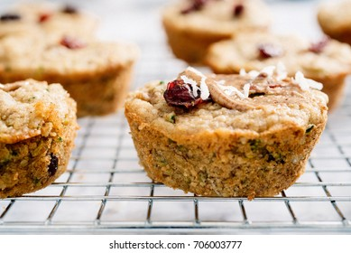 A flourless zucchini cranberry coconut muffin on wire cooling rack spread with almond butter and topped with a dried cranberry.