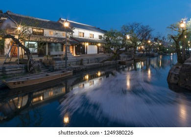 Flow of cherry blossom petals in the canal of the Bikan Historical Quarter at night, Kurashiki, Japan