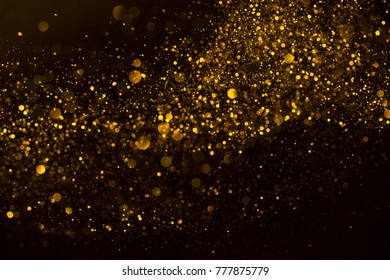 Flow wave of golden glitter dust shiny sparkle bokeh abstract background