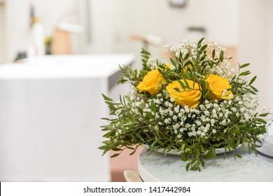 A flower arrangement with baby's breath Gypsophila paniculata, yellow roses and green leafs. With copy space to the left.