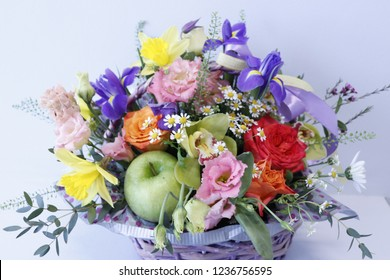 Flower arrangement in the basket. Orchids, irises, roses, eustoma and green apple