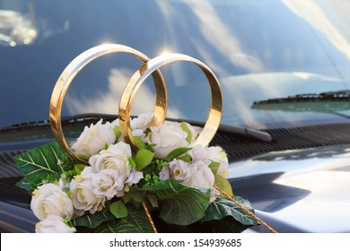 A flower arrangement with big golden rings for a wedding on a black car